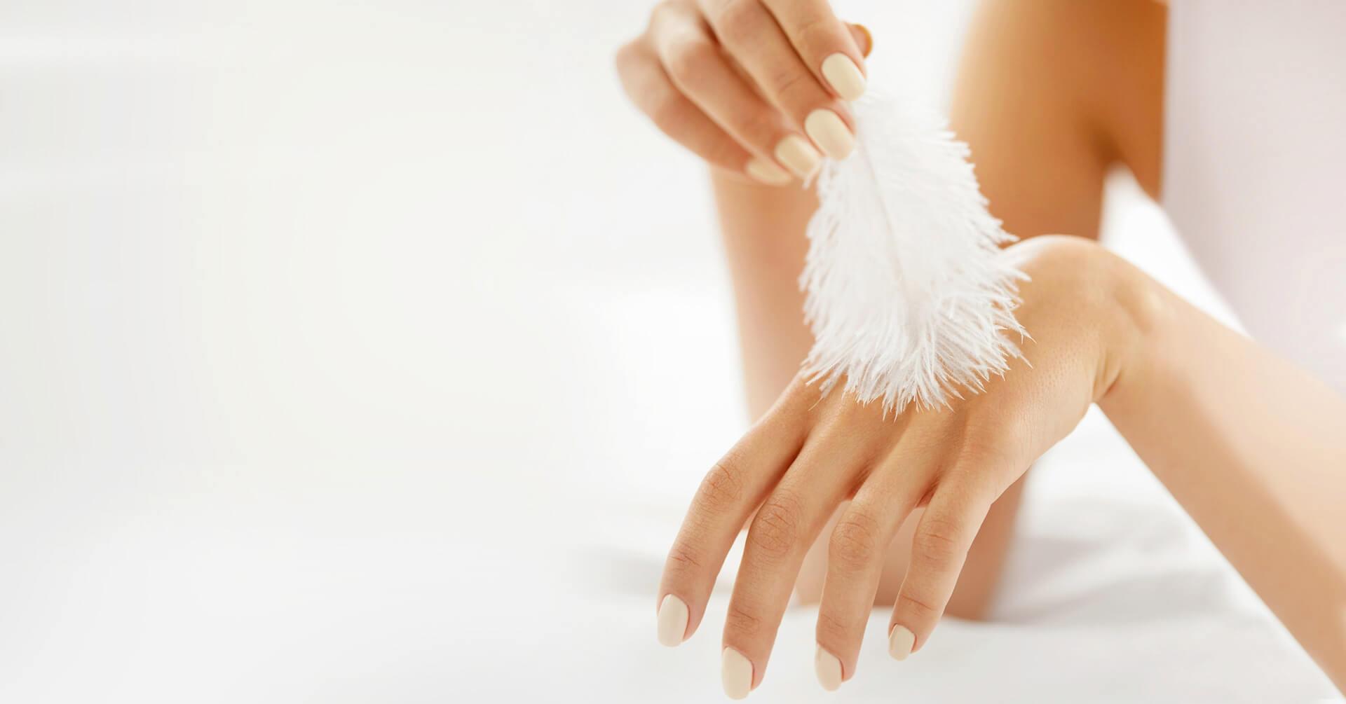 kobieta dotykająca swojej dłoni piórkiem