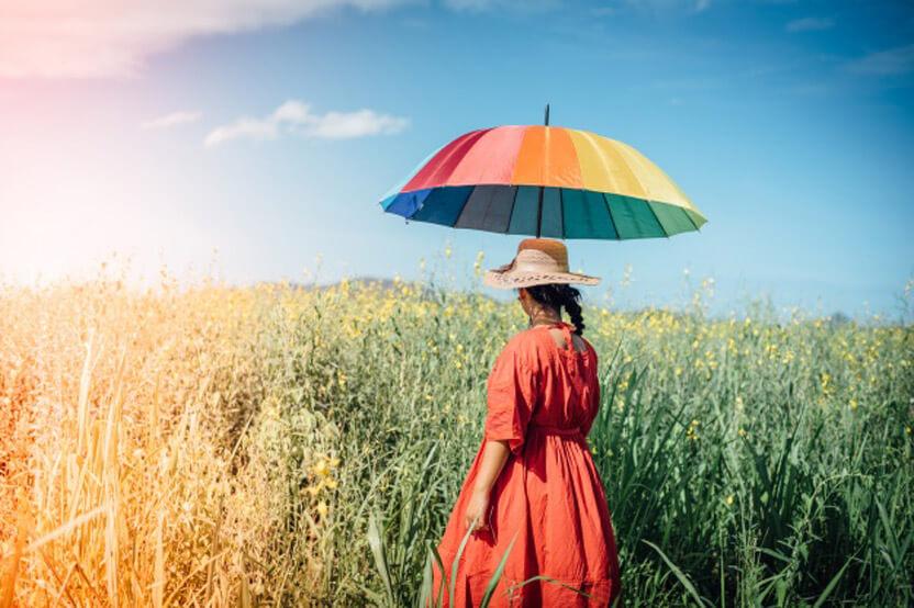 kobieta wczerwonej sukience itęczowym parasolem pośród kłosów zbóż