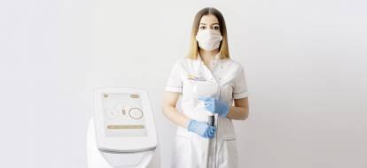 Kosmetolog depilacja.pl w trakcie epidemii stoi przy laserze SPEC3 Hybrid w maseczce i rękawiczkach.