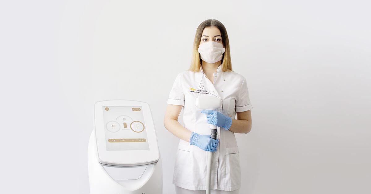 Kosmetolog depilacja.pl wtrakcie epidemii stoi przy laserze SPEC3 Hybrid wmaseczce irękawiczkach.