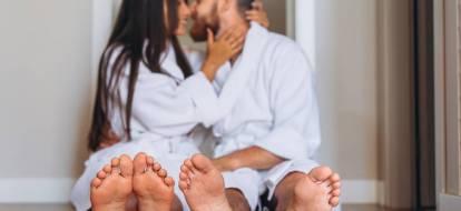 Para z gołymi stopami, w białych szlafrokach siedzi na ziemi całując się.