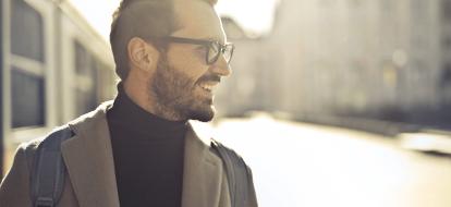 Mężczyzna z brodą i okularach widoczny z prawego profilu uśmiecha się na tle miasta.