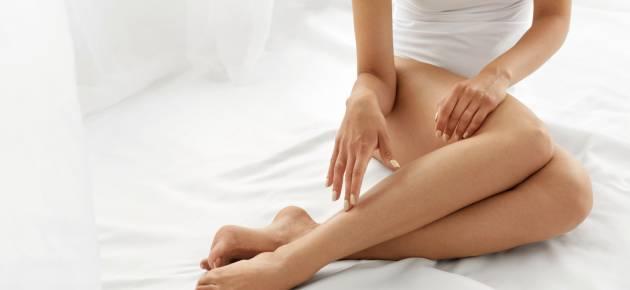 kobieta siedząca na łóżku z białą pościelą dotykająca swoich nóg