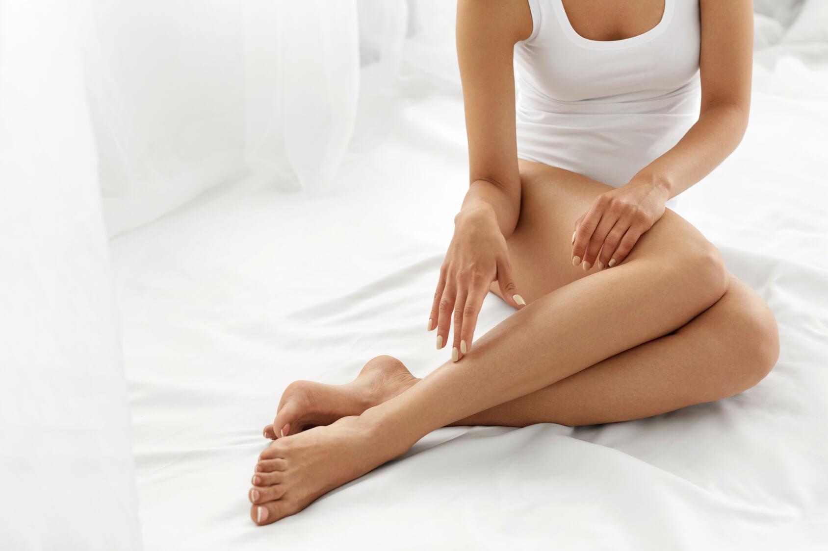 kobieta siedząca na łóżku zbiałą pościelą dotykająca swoich nóg