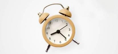 Brązowy budzik na białym tle, wskazujący godzinę dziewiątą dwadzieścia.