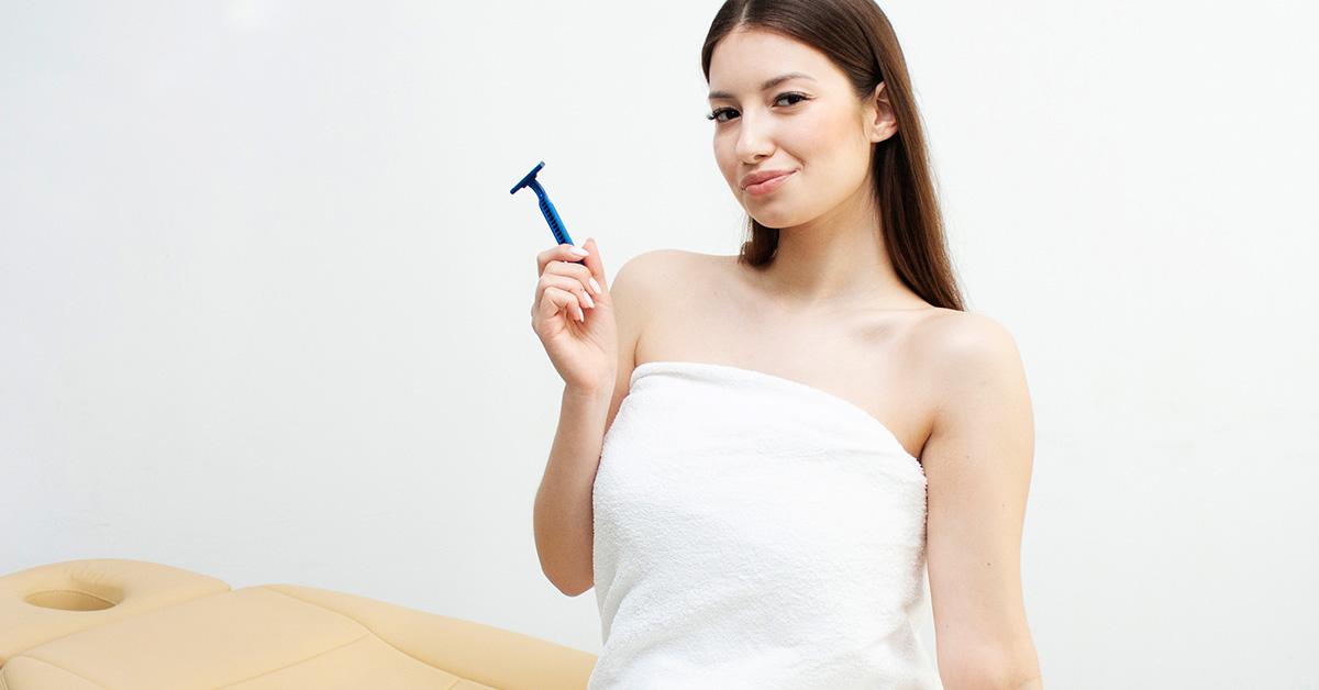 Dziewczyna wbiałym ręczniku trzymająca maszynkę do golenia.