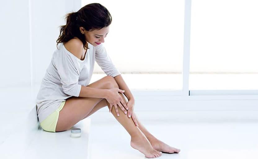 kobieta wjasnymi ubiorze trzymająca się za swoje nogi