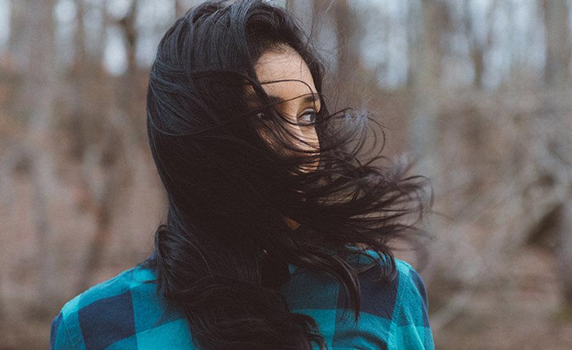 rozwiane czarne włosy młodej kobiety wlesie