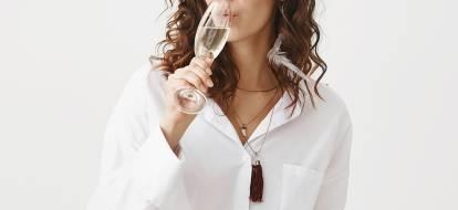 Dziewczyna w białej koszuli pije szampana.