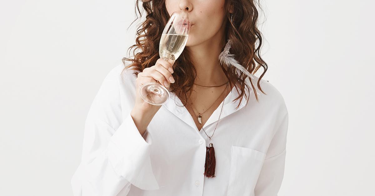 Dziewczyna wbiałej koszuli pije szampana.