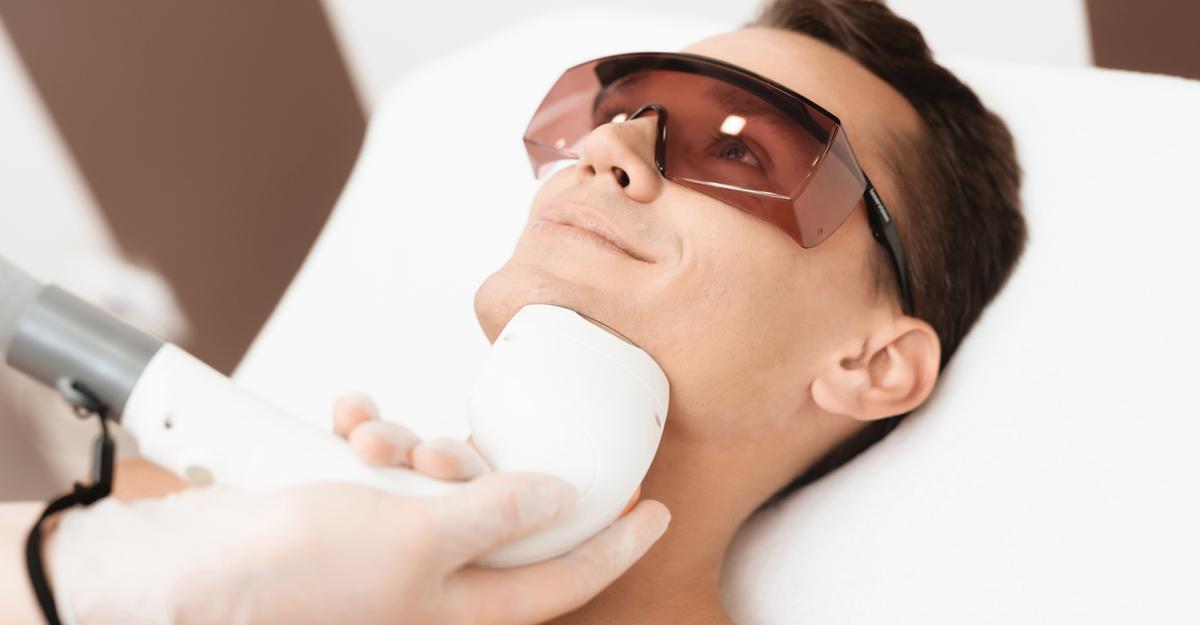 Depilacja laserowa brody uprzystojnego, uśmiechniętego bruneta.