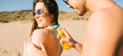 Para na plaży. Chłopak smaruje dziewczynie plecy olejkiem do opalania.