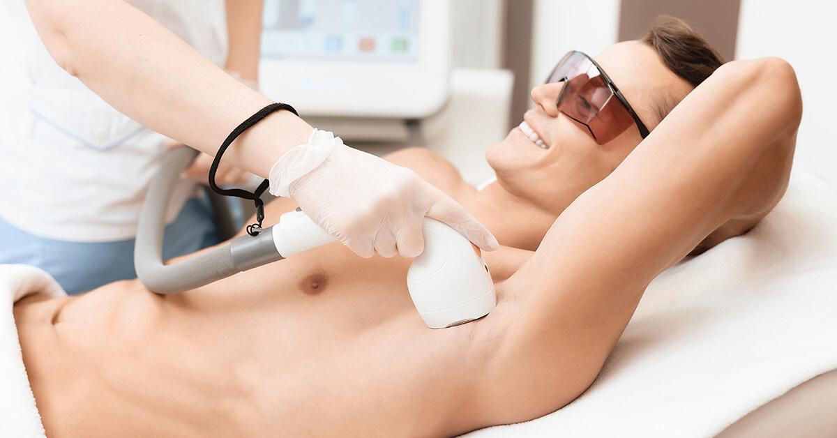 Mężczyzna na zabiegu depilacji laserowej pach.