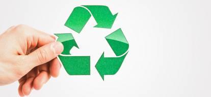 Dłoń trzymająca znak recyclingu.