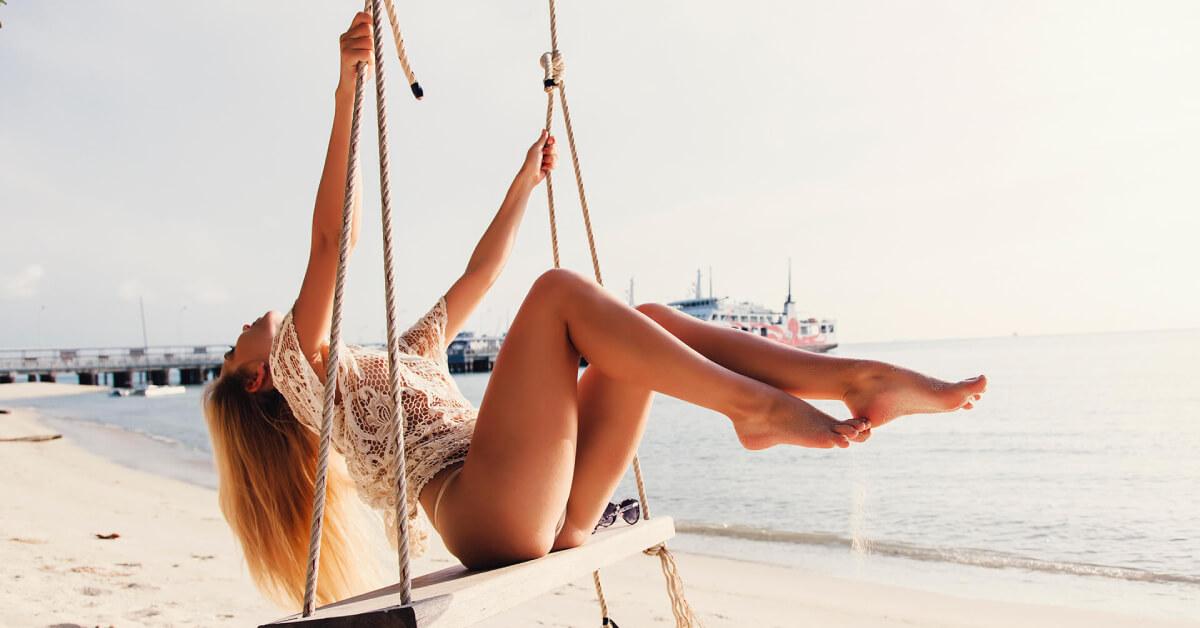 Blondynka na huśtawce na egzotycznej plaży.