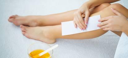 Kobieta robi depilację woskiem na łydce.
