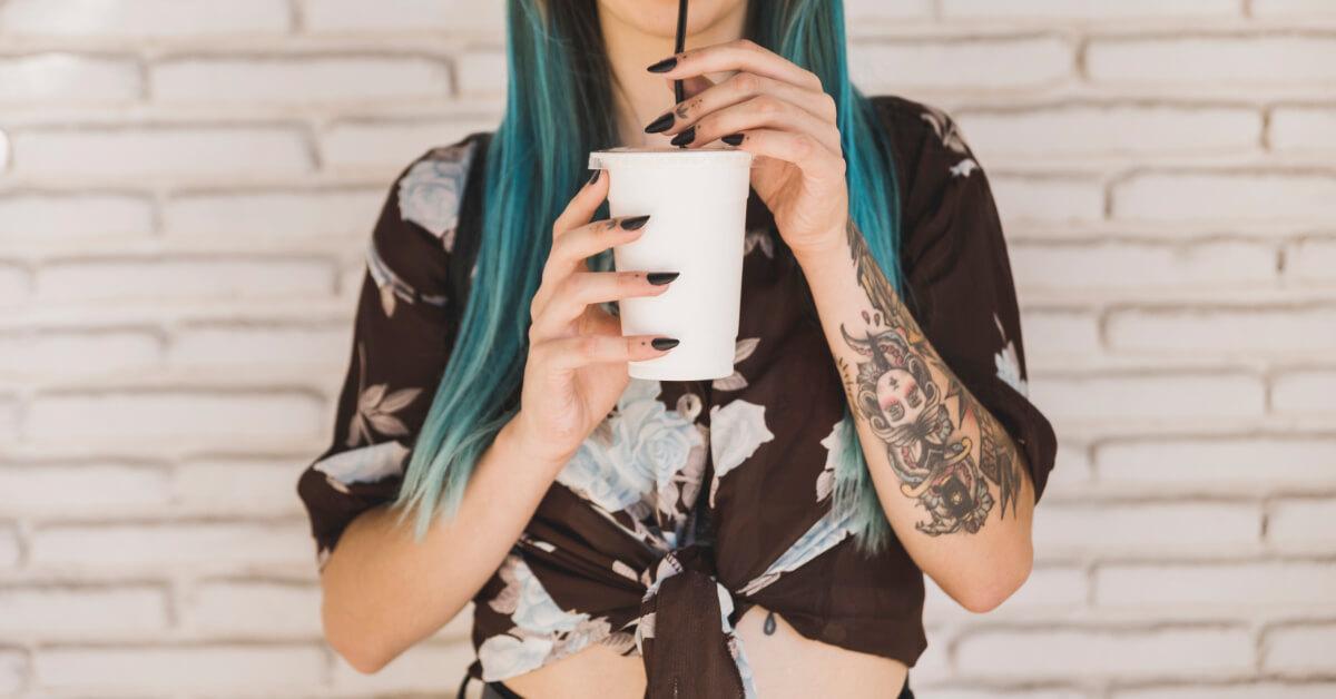 Dziewczyna zwytatuowaną ręką izielonymi włosami pije napój przez słomkę.