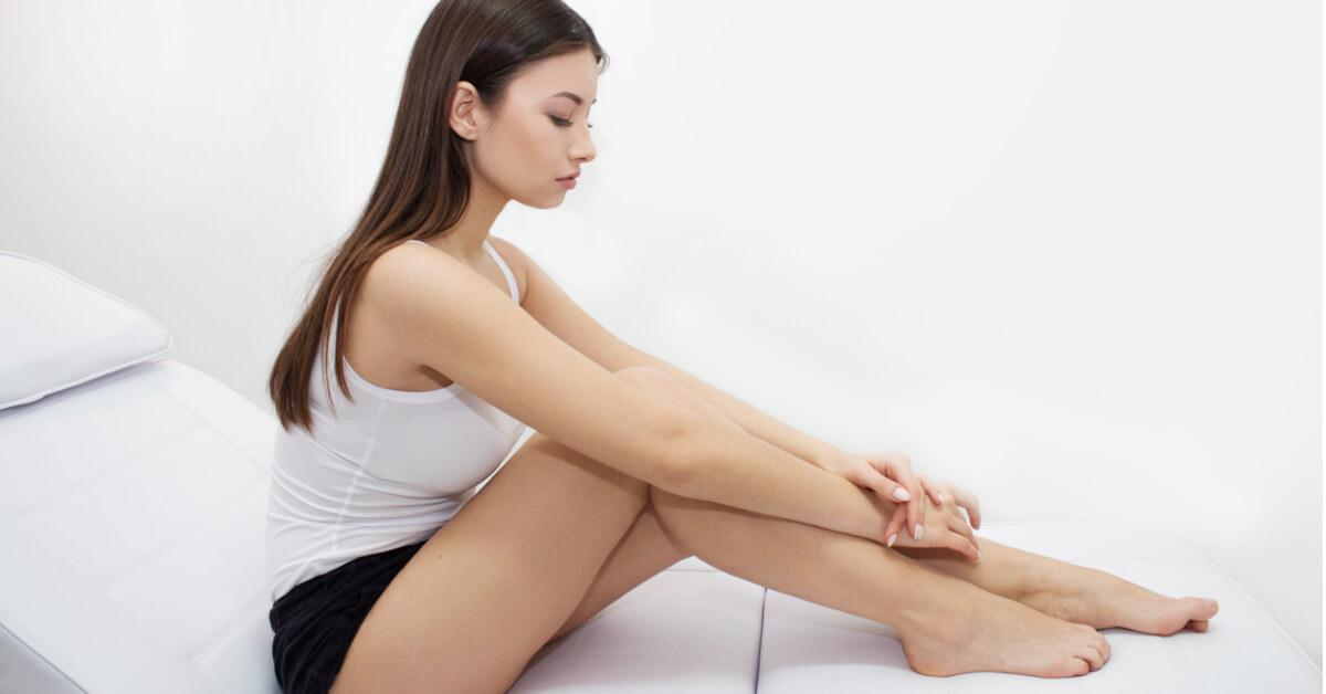 Smutna dziewczyna spogląda na swoje nogi.