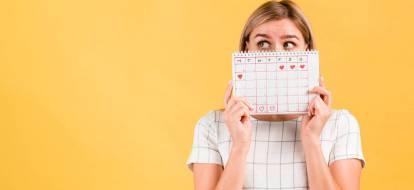 Dziewczyna na żółtym tle zasłania twarz kalendarzem z zaznaczoną datą miesiączki.