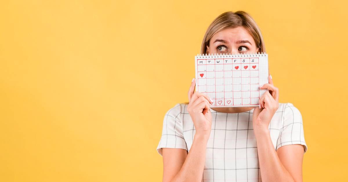 Dziewczyna na żółtym tle zasłania twarz kalendarzem zzaznaczoną datą miesiączki.
