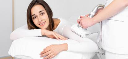 Zadowolona dziewczyna w specjalnym kostiumie podczas zabiegu endermologii w salonie depilacja.pl