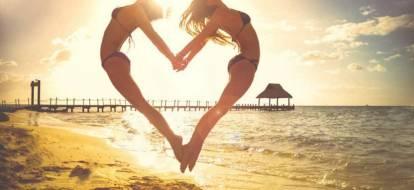 dwie kobiety ułożone w serce na tle molo podczas zachodu słońca