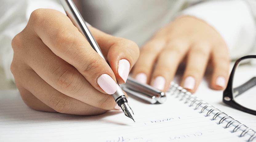 Zbliżenie na dłonie zjasnymi paznokciami. Prawa ręka trzyma pióro irobi notatki.