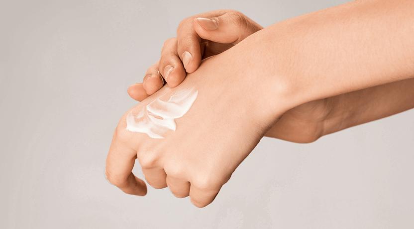 Zbliżenie na dłonie znałożonym kremem.