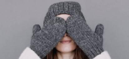 Dziewczyna w grubych szarych rękawiczkach z jednym palcem i w grubej czapce zasłania twarz.