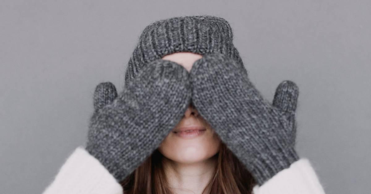Dziewczyna wgrubych szarych rękawiczkach zjednym palcem iwgrubej czapce zasłania twarz.
