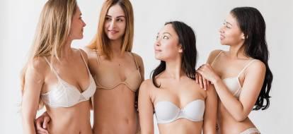 Cztery dziewczyny o różnych fototypach pozują w w bieliźnie na szarym tle.