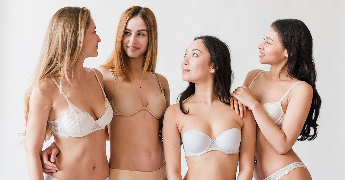 Cztery dziewczyny oróżnych fototypach pozują wwbieliźnie na szarym tle.