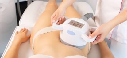 Kosmetolog przeprowadza zabieg enndermologii na brzuch korzystając z głowicy ultradźwiękowej.