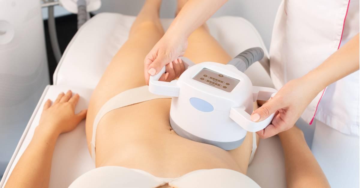 Kosmetolog przeprowadza zabieg enndermologii na brzuch korzystając zgłowicy ultradźwiękowej.