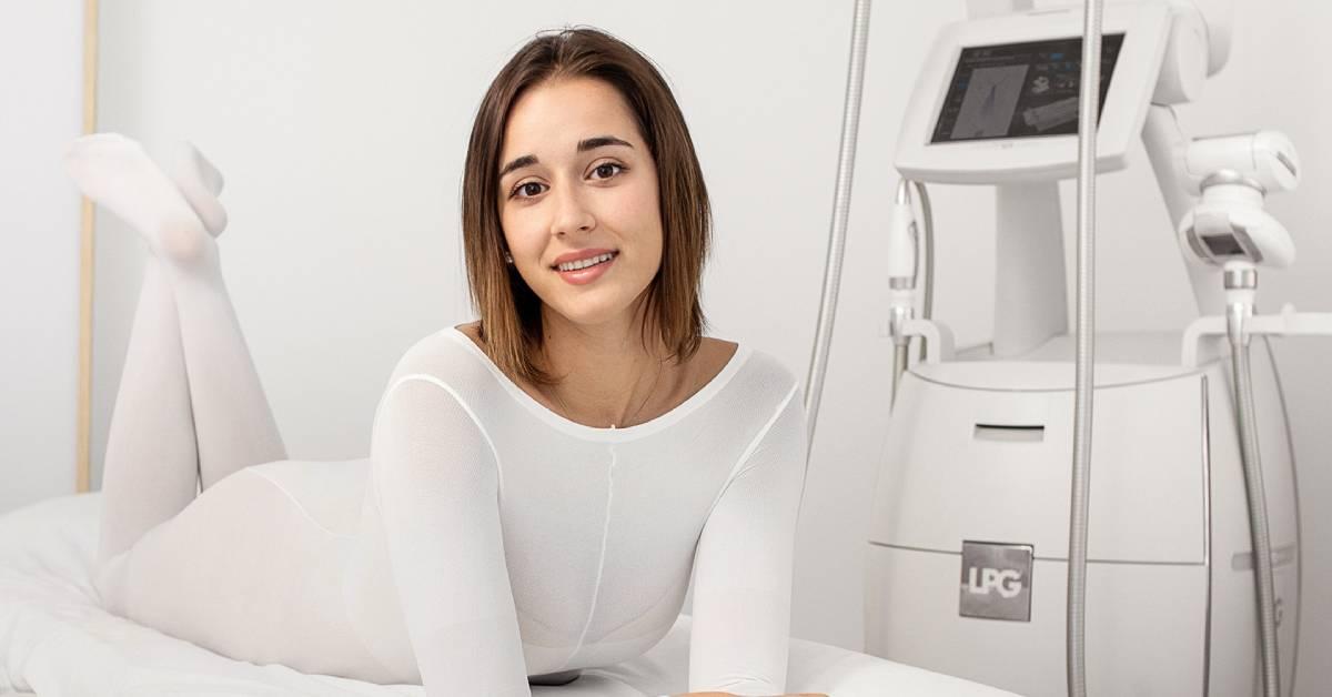 Uśmiechnięta brunetka na łóżku zabiegowym obok urządzenia do endermologii.