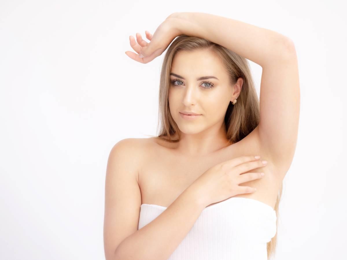 Dziewczyna pokazuje gładką skóra pod pachami po depilacji laserowej.
