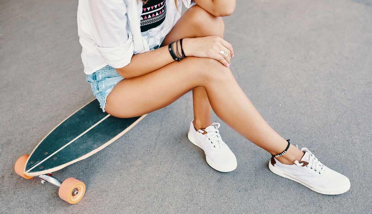Nastolatka wszortach siedzi na longboardzie na chodniku.