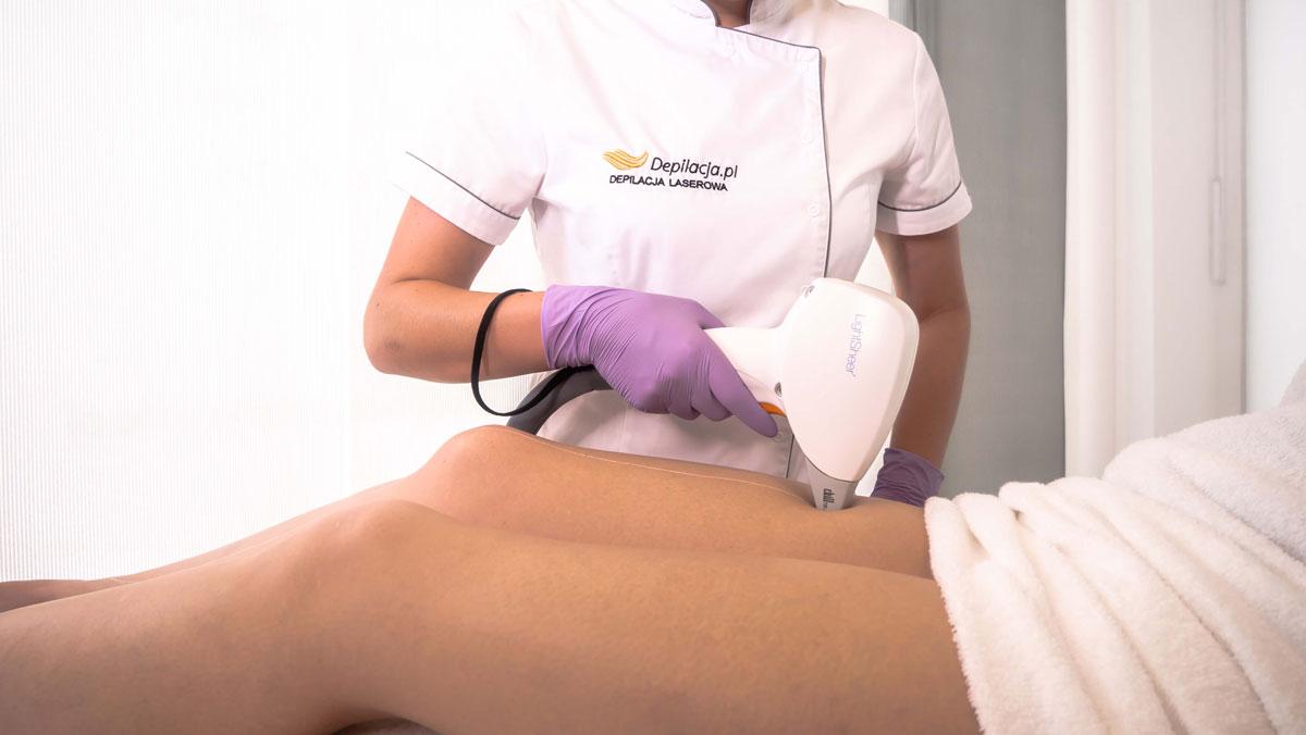 Kosmetolog przeprowadza zabieg depilacji laserowej na udach pacjentki.