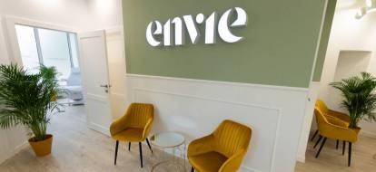 Poczekalnia kliniki medycyny estetycznej. Na oliwkowej ścianie duży napis Envie, pod napisem dwa musztardowe fotele.