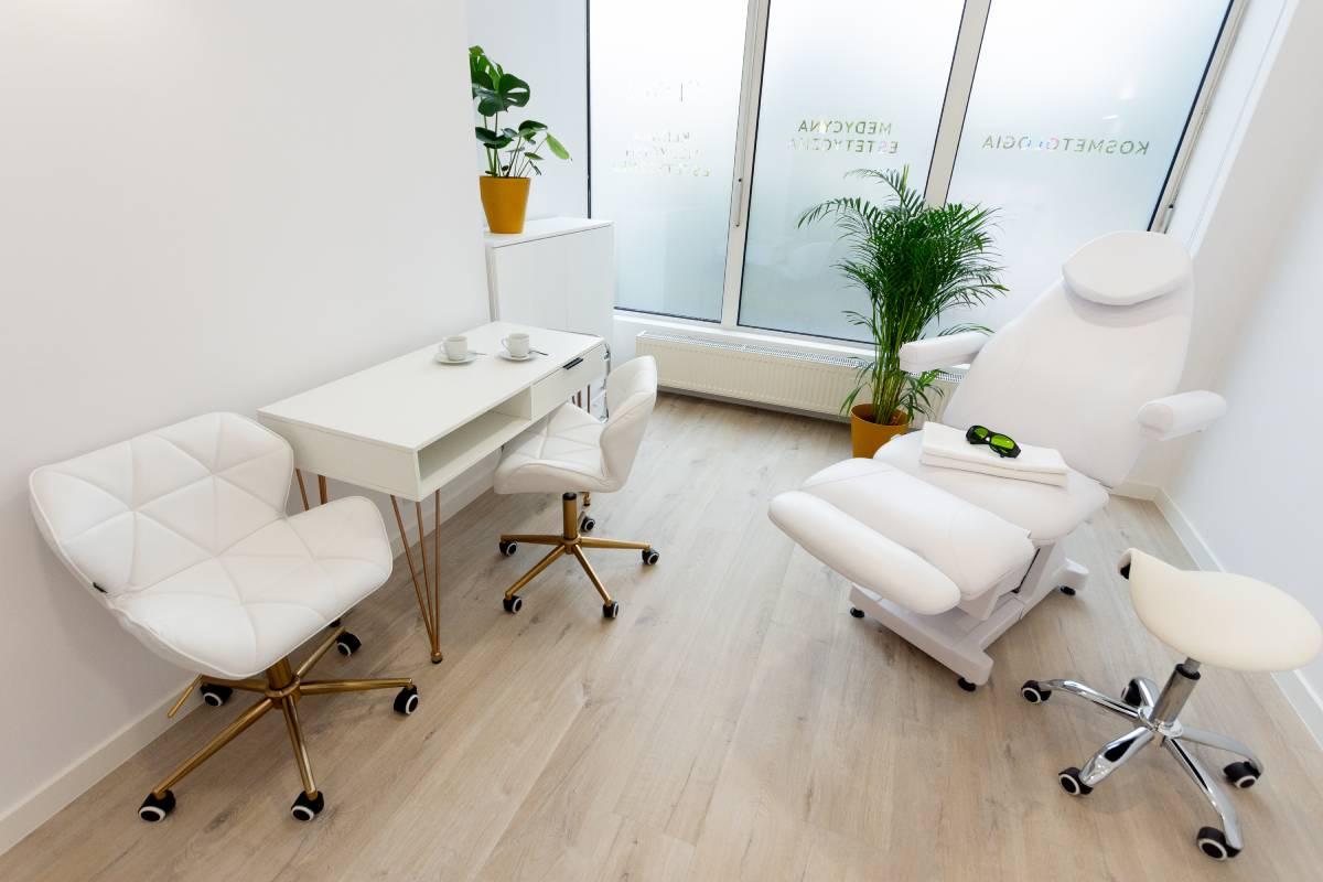 Gabinet depilacji laserowej. Białe ściany, fotel zabiegowy oraz laser do depilacji.