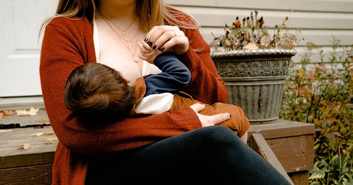Kobieta karmiąca dziecko piersią na schodkach wogrodzie.