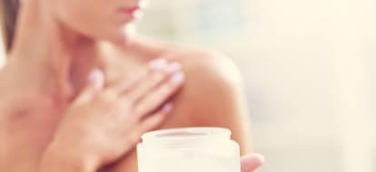 kobieta podczas nakładania kosmetyku na ramię