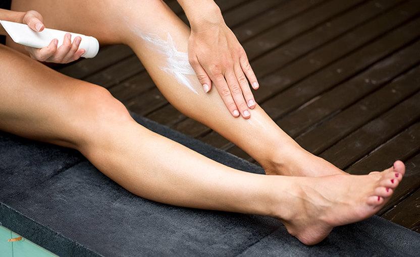 Obrazek przedstawiający kobietę, która smaruje nogi kremem do depilacji