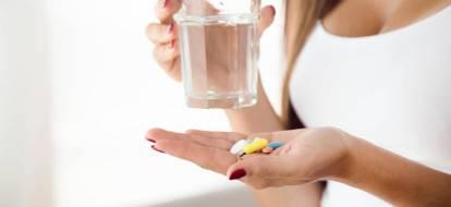 Zbliżenie na dłonie kobiety, w których trzyma leki oraz szklankę z wodą.