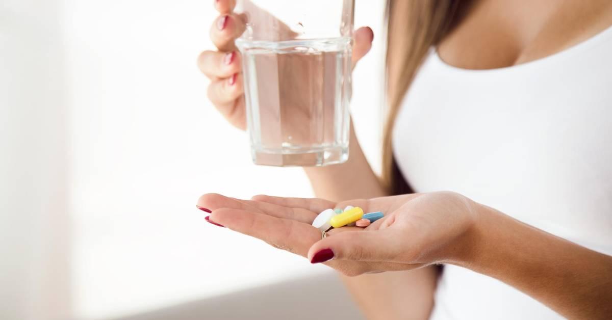 Zbliżenie na dłonie kobiety, wktórych trzyma leki oraz szklankę zwodą.