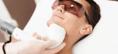 Uśmiechnięty brunet w trakcie zabiegu depilacji laserowej brody.