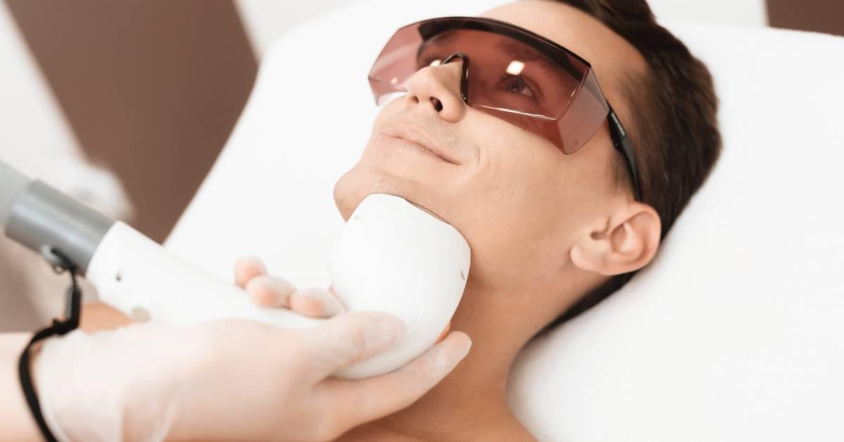 Uśmiechnięty brunet wtrakcie zabiegu depilacji laserowej brody.