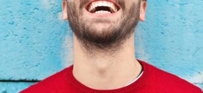 Kadr na usta i szyję roześmianego brodatego mężczyzny w czerwonej bluzie na niebieskim tle.