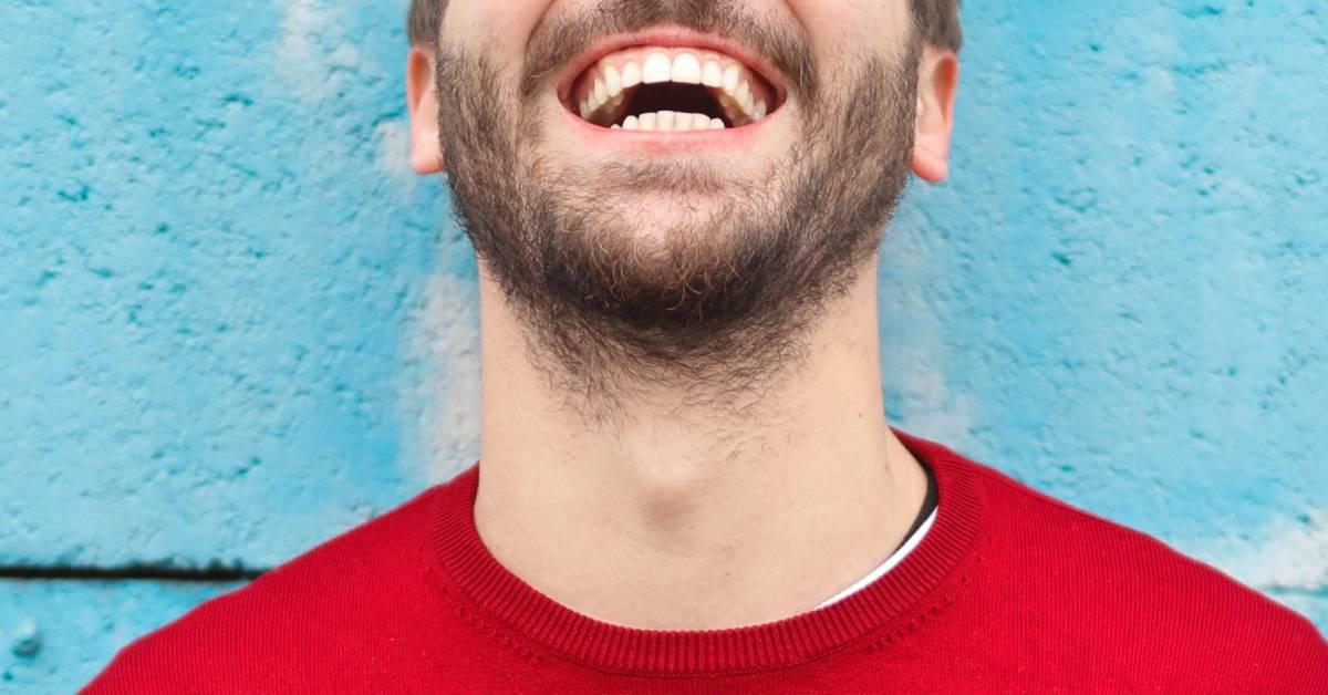 Kadr na usta iszyję roześmianego brodatego mężczyzny wczerwonej bluzie na niebieskim tle.