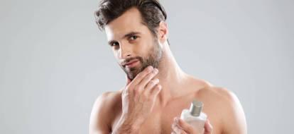 Przystojny mężczyzna dotyka twarzy z zarostem trzymając w dłoni butelkę płynu po goleniu.